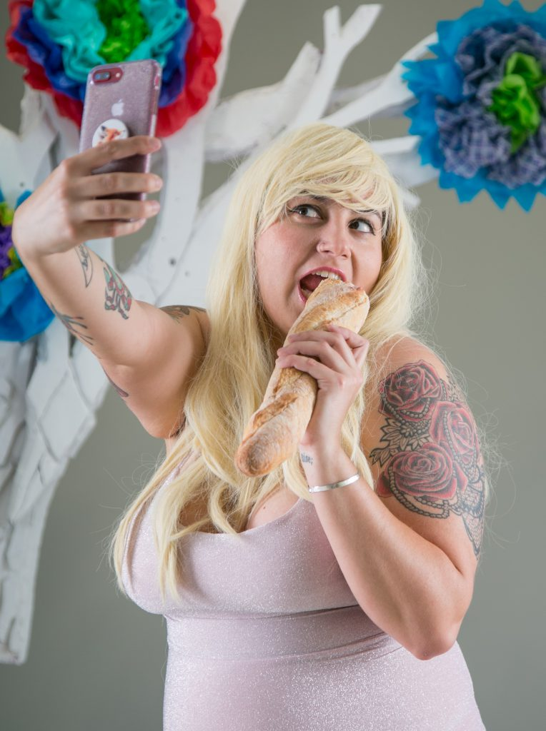 Sexy lady eats a baguette while taking picture with her phone.